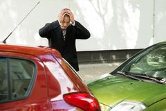 Stressed driver looking at car after traffic collision Royalty Free Stock Image