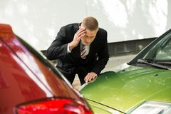 Stressed driver looking at car after traffic collision. Stressed Driver Standing At Roadside After Traffic Accident Stock Photography