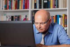 Stressed elderly man staring on computer Stock Photo