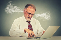 Stressed elderly old man using computer blowing steam from ears Royalty Free Stock Image
