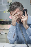 Stressed employee on the phone Stock Photo