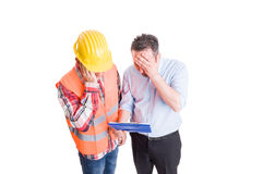 Stressed engineer and upset builder checking clipboard Stock Photo