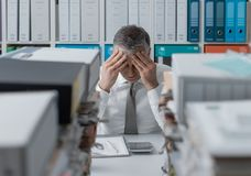 Stressed business executive and piles of paperwork. Stressed exhausted business executive in the office overloaded with work, he has piles of paperwork on the royalty free stock photo