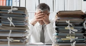 Stressed business executive and piles of paperwork. Stressed exhausted business executive in the office overloaded with work, he has piles of paperwork on the stock images