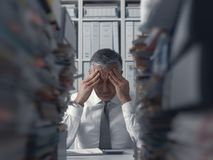 Stressed business executive and piles of paperwork. Stressed exhausted business executive in the office overloaded with work, he has piles of paperwork on the stock photos