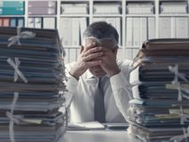 Stressed business executive and piles of paperwork. Stressed exhausted business executive in the office overloaded with work, he has stacks of paperwork on the royalty free stock images