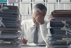 Stressed business executive and piles of paperwork. Stressed exhausted business executive in the office overloaded with work, he has stacks of paperwork on the stock image