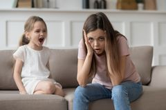 Stressed mother feeling desperate about screaming stubborn kid daughter tantrum. Stressed exhausted mother looking at camera feeling desperate about screaming royalty free stock photos