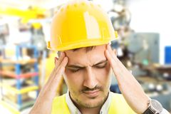 Stressed factory worker suffering head pain migraine or headache royalty free stock image