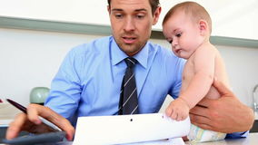 Stressed father calculating bills with his baby