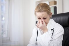 Stressed Female Doctor Holding her Nose Bridge Royalty Free Stock Photos