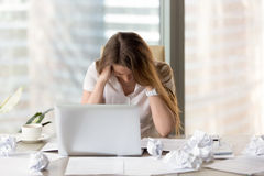 Stressed female entrepreneur in creativity crisis. Desperate businesswoman sitting at the desk with laptop and crumpled paper. Female office worker suffers royalty free stock photography