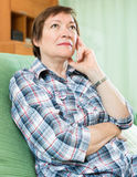 Stressed female pensioner on couch Stock Photo