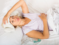 Stressed female pensioner lays  with headache Royalty Free Stock Image