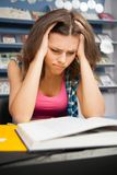 Stressed female student in a library Royalty Free Stock Photos