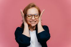 Stressed female teacher covers ears, has headache because of noisy pupils, clenches teeth, ignores noise, wears optical glasses, royalty free stock photos