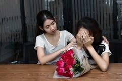 Stressed frustró a la mujer asiática joven que apoyaba al amigo femenino gritador presionado en sala de estar Rómpase para arriba Fotos de archivo