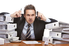 Stressed frustrated business man with telephones Royalty Free Stock Image