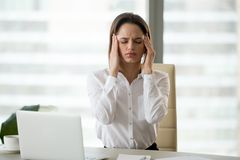 Stressed frustrated female employee feeling headache or migraine. Stressed frustrated female employee feeling strong headache at workplace massaging temples royalty free stock photography