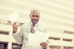 Stressed frustrated man holding looking at documents Royalty Free Stock Image