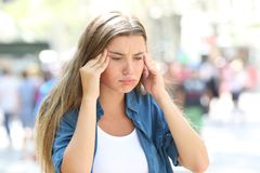 Girl suffering head ache in the street royalty free stock images