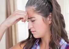 Stressed girl with sore head by window Royalty Free Stock Image