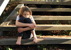 Stressed girl on wooden stairs. Stressed little girl - barefoot in sitting on wooden stairs Stock Images