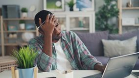 Stressed guy African American freelance worker is using laptop typing then touching head feeling tired and unhappy