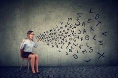 Stressed ha isolato l'impiegato femminile che si siede su una sedia che grida nella frustrazione fotografia stock