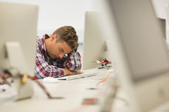 Stressed handsome student studying in the computer room Royalty Free Stock Images