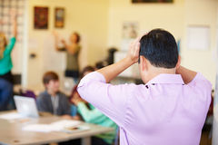 Stressed High School Teacher Trying To Control Class Stock Photo