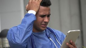 Stressed Hispanic Male Surgeon With Tablet. A handsome adult hispanic man stock footage