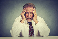 Stressed hopeless elderly business man in depression sitting at the office table Royalty Free Stock Photography