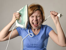 Stressed housewife or maid domestic service woman holding upset iron strangling neck with cable Stock Images