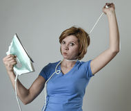 Stressed housewife or maid domestic service woman holding upset iron strangling neck with cable Stock Photo