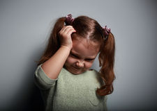 Stressed kid girl with headache holding hand the head. On dark background royalty free stock photos