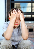 Stressed Kid outdoor. Stressed Kid sit on the City Street royalty free stock images