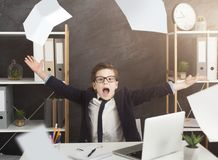 Stressed little boy in suit throwing papers in air. Bureaucracy, exhausting paperwork. Stressed little boy in suit throwing papers in air, sitting at office royalty free stock photo