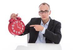 Stressed lokalisierte den Geschäftsmann, der auf Uhr zeigt 4 Uhr nachher Stockfoto