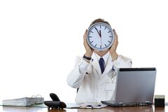 Stressed male doctor in office under time pressure. Stressed medical holds clock in front of face because of time pressure.Isolated on white background Stock Images