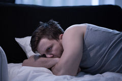 Stressed male with insomnia. Photo of stressed male with insomnia lying in bed Stock Photography