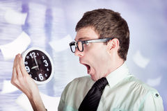 Stressed male office worker holding overtime clock Stock Images