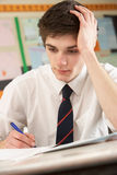 Stressed Male Teenage Student Studying. In Classroom Stock Photos