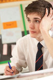 Stressed Male Teenage Student Studying. In Classroom Royalty Free Stock Photos
