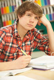 Stressed Male Teenage Student Studying. In Classroom Stock Photography