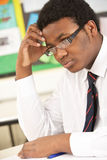 Stressed Male Teenage Student Studying. In Classroom Royalty Free Stock Image