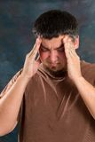 Stressed Man. Man stressed by work and tension of the day rubs his forehead in pain Royalty Free Stock Photos