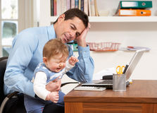 Stressed Man With Baby Working From Home. Using Laptop Royalty Free Stock Photography