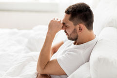 Stressed man in bed at home. People, bedtime and rest concept - stressed man in bed at home Stock Photography