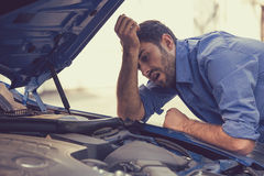 Stressed man with broken car looking at failed engine Royalty Free Stock Photos